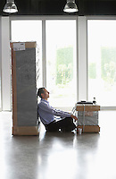 Man with laptop resting between packages in empty office