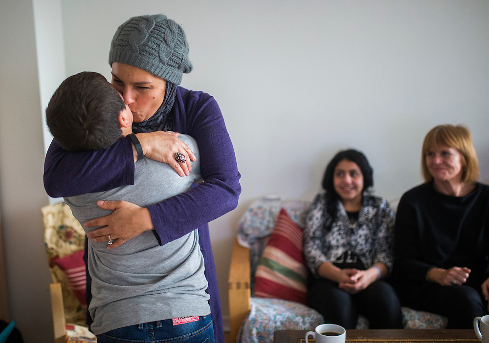 Syrian refugee Nasimi Batal Al Hasan is greeted by a english translator Mariela Barazi inside their apartment in Mississauga, Ontario, Canada, Thursday January 21, 2016.   (Mark Blinch for the BBC)