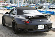 Beckham Porsche Up For Sale<br /> <br /> Footie star David Beckhams distinctive customised Porsche 911 in matt black paint, is up for sale on eBay. A dealer in California has put the car on the popular auction site. Chequered Flag International said this is the ultimate 2008 Porsche 911 Turbo Cabriolet purchased new by world famous soccer superstar David Beckham. This is a well known car that David has been photographed driving in LA for the last 3 years. Purchased new at Beverly Hills Porsche and then  personalized with no expense spared; Painted in Matte Black, some expensive off set three piece rims  and Techart exhaust were fitted, custom made silver '23' emblems are featured throughout (on the front hood, deck lid, rims and steering wheel), also embroided on the front and rear seats and custom fitted floor mats. Other upgrades include bass speakers hidden under the rear jump seats. This spectacular 911 Turbo was ordered with Tiptronic S transmission, heated front seats, parking assist, sport chrono/package, module for telephone PCM, remote CD changer, 6 disc and thicker leather steering wheel. It said there has been no damage or issues with the car. The eBay advert adds: This is a very rare opportunity to acquire a unique supercar with unparalleled celebrity history. We have all the books, keys and window sticker.At the time of writing, there had been nine bids taking the total to $110,100 but the reserve had still not been met for the car in Marina Del Rey. It has six days still to run.<br /> ©Exclusivepix