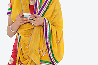 Midsection of woman in Indian clothing using cell phone over gray background