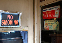 "Old signs advertising cigarettes next to a new sign reading ""no smoking"" are seen at entrance to the tavern in the village of Monowi, Nebraska April 27, 2011. Elsie Eiler, who runs the tavern, is the sole person living in Monowi making it the only incorporated town, village or city in the United States with just one resident.  REUTERS/Rick Wilking (UNITED STATES)"