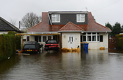 The front of a house with sandbags on the front door as the UK starts to sink. Photo taken on the edge of Wraysbury, UK. Tuesday, 11th February 2014. Picture by Andrew Parsons / i-Images