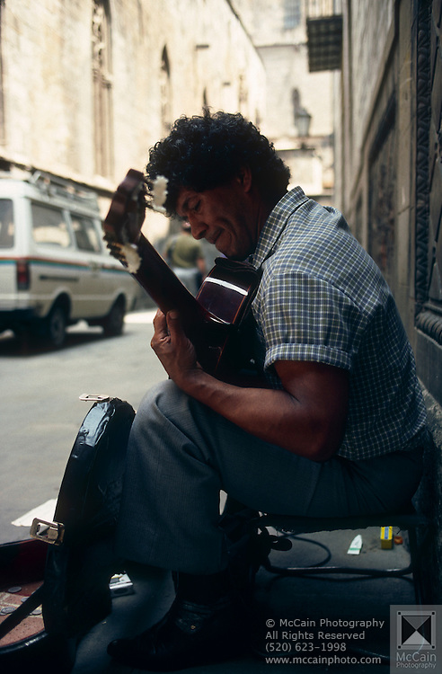 Street performer playing guitar in the streets of the Barri Gòtic ('Gothic Quarter' in Catalan; Castilian: Barrio Gótico), the centre of the old city of Barcelona, Spain...Media Usage:.Subject photograph(s) are copyrighted Edward McCain. All rights are reserved except those specifically granted by McCain Photography in writing...McCain Photography.211 S 4th Avenue.Tucson, AZ 85701-2103.(520) 623-1998.mobile: (520) 990-0999.fax: (520) 623-1190.http://www.mccainphoto.com.edward@mccainphoto.com