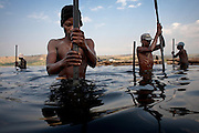 Men use metal bars to extract rock salt from the bed of Lake Katwe, Uganda. The rock is extracted three days a week from the lake with workers paid by weight at approximately $2 per 100kg, of which the government takes a percenage. All men work from dusk till dawn with a strong worker extracting 400 kg per day. Skin damage is a major problem for people working at Lake Katwe as chemicals in the water eat away at any nick or cut and also cause nerve damage.
