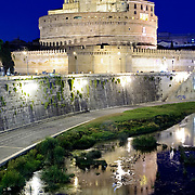 The lights of the Castel Sant'Angelo are reflected on the still waters of the Tiber in Rome, Italy.