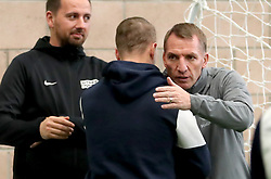 Celtic's Leigh Griffiths (centre) is hugged by manager Brendan Rodgers (right) alongside Street Soccer founder and CEO David Duke (left) as the men and women Street Soccer teams take part in a special training session at Lennoxtown, Glasgow.
