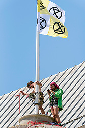 "© Licensed to London News Pictures;25/06/2020; Bristol, UK. Five Extinction Rebellion activists have climbed up the central dome of Bristol City Hall early this morning and say they will stay up there until Bristol City Council commits to ensuring legally clean air in every suburb of the city by April 2021. Extinction Rebellion's Five a Week campaign for clean air is highlighting the number of premature deaths in Bristol due to air pollution. They have set up 296 pairs of shoes on College Green in front of City Hall with the message ""296 Deaths a Year"" which the campaigners say is the number of people who die each year due to air pollution in the city. Extinction Rebellion demand urgent action from Bristol City Council & WECA (West of England Combined Authority) to protect people's lungs and protect the planet, saying health is intrinsically linked to the health of the environment. XR want Clean Air Equality for Life, not just for the coronavirus Covid-19 lockdown, saying there is a unique opportunity as we come out of lockdown to envision a Bristol that puts people's health and the health of the planet first, and put pressure on elected officials to help build the city back better. Photo credit: Simon Chapman/LNP."