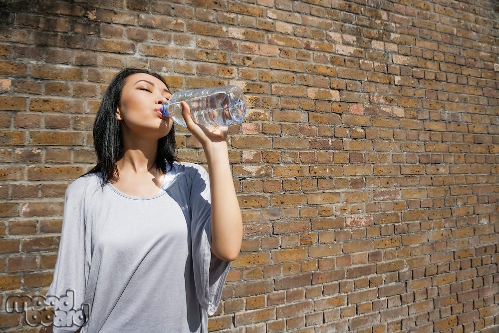 Beautiful young woman drinking water against brick wall