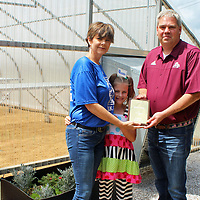 Mississippi Peanuts owner Brian Atkins receives a plaque of appreciation from Hamilton Parent Teacher Organization President Kim Guest. Funding provided through Atkins' annual agriculture night auction helped to build the greenhouse at Hamilton High School pictured behind them. Joining Guest in the presentation was her daughter Cricket.
