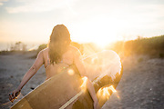 A young woman enjoying a sunset at the beach with her surfboard