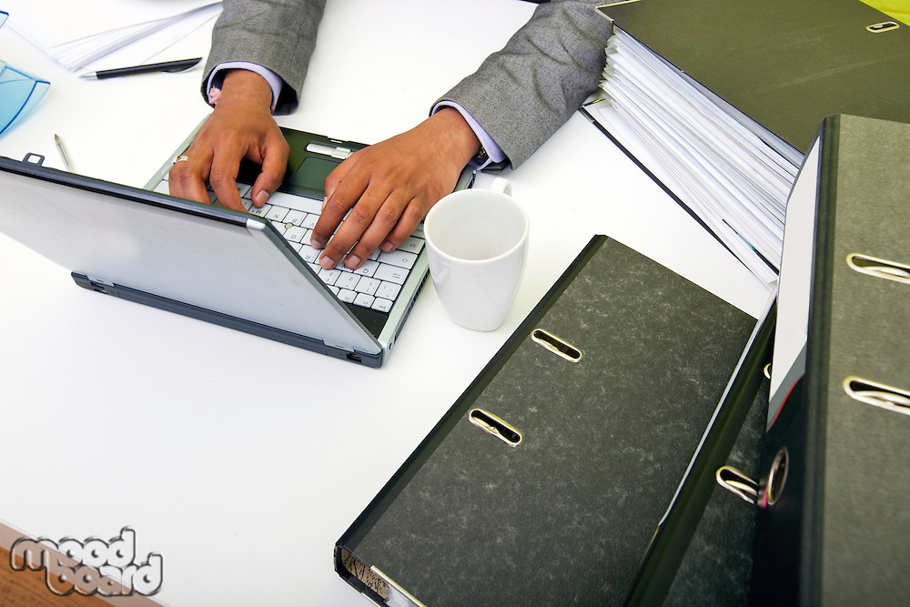 Close up of Indian mans hands typing on laptop with folders and mug