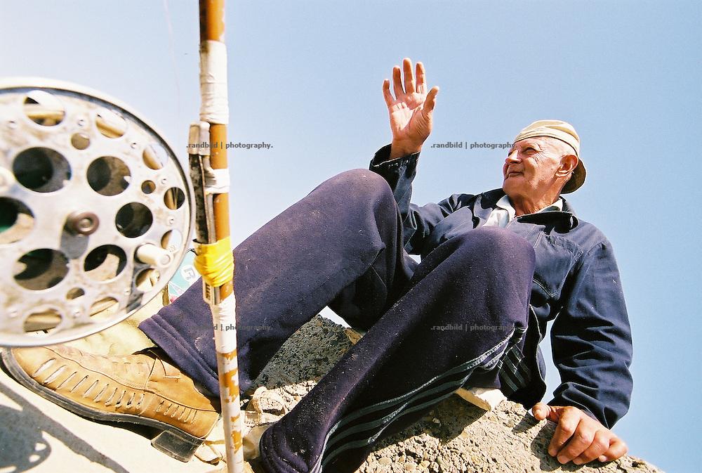 Im Hafen der aserbaidschanischen Hauptstadt Baku angeln auf einer Kaimauer alte Herren. Das Wasser ist von der Ölförderung im Kaspischen Meer verschmutz. Entsprechend keine Fische gehen ihnen an den Haken...Fisherman in the habour of Baku, Aserbaijan.