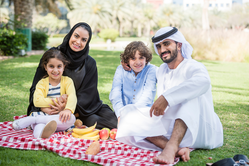 Portrait of arab Emirati family of mother, father and two children sitting outdoors having picnic. The parents wear traditional thobe clothing of Abaya for the woman and Kandura ghutra and agal for the man. They are happy and smiling to camera.