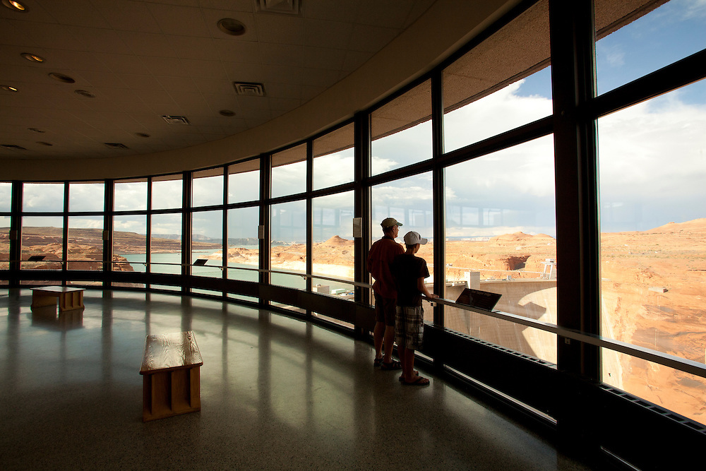 North America, Arizona, Page, Glen Canyon Dam Visitor Center.  Father and son look out huge wall of windows to dam.