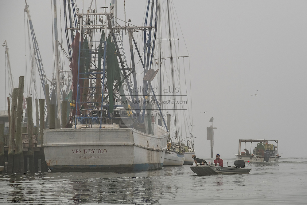 Fishermen head out on Shem Creek during a foggy winter morning in Charleston, South Carolina.