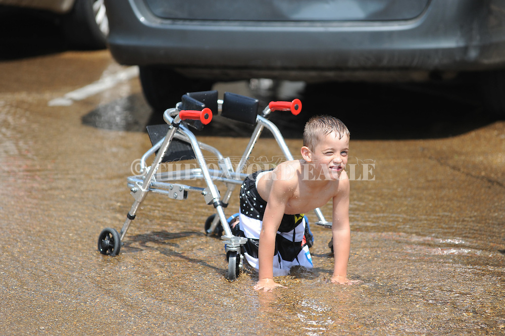 Kids play in water from a fire truck at Baptist Healthplex in Oxford, Miss. on Friday, May 25, 2012.  .