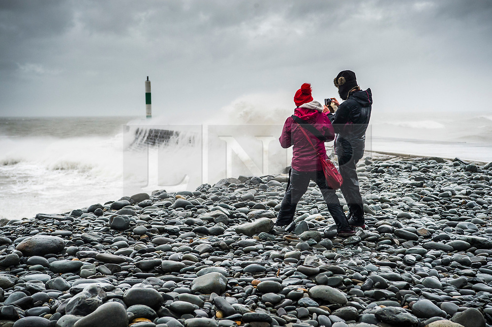 © Licensed to London News Pictures. 08/02/2019. Aberystwyth, UK. Two people in rain coats brave the conditions as they watch gale force south-westerly winds bring huge waves to batter the sea defences at Aberystwyth on the Cardigan Bay coast, West Wales at high tide as Stormy Erik hits the UK. Photo credit: Keith Morris/LNP