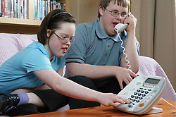 Teenage Downs Syndrome boy and girl using a large button telephone,