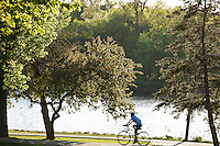 Summer scene as a biker rides along the park trails of Lake of the Isles in Minneapolis, Minnesota on a warm springtime day.