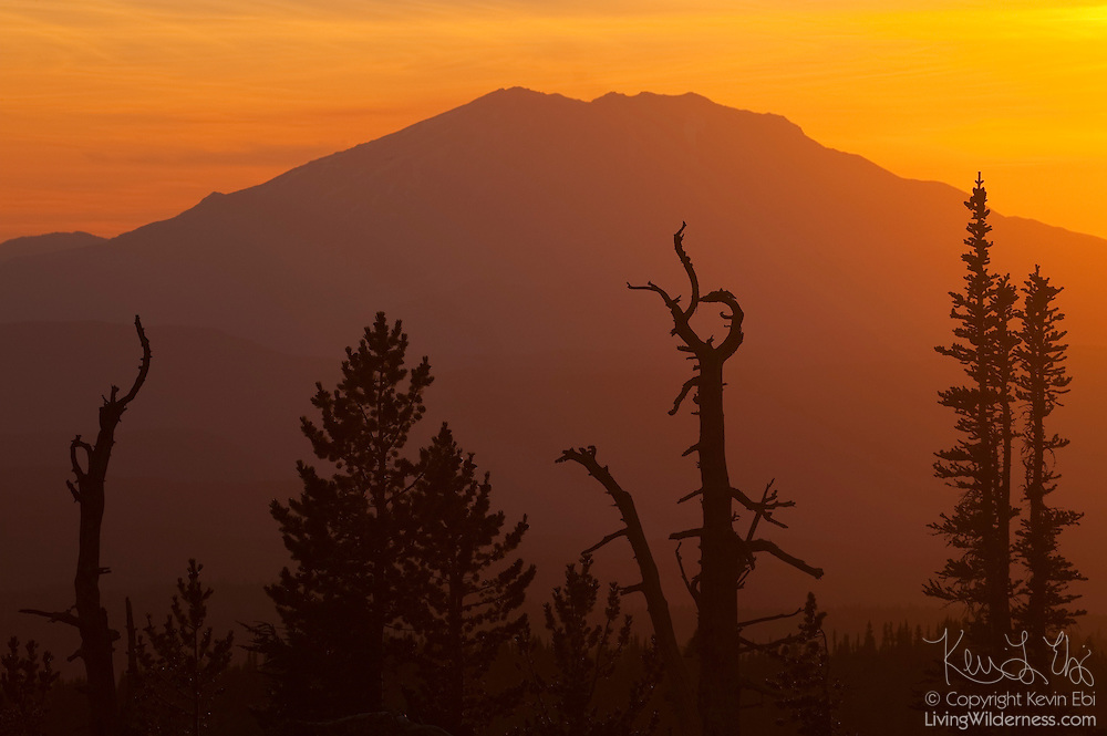 The sun sets behind Mount St. Helens, rendering it in silhouette in this view from Mount Adams, Washington.