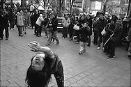 A woman dances, as if possessed, to the amusement and bewilderment of passerbys outside Shibuya train station. Tokyo, Japan.