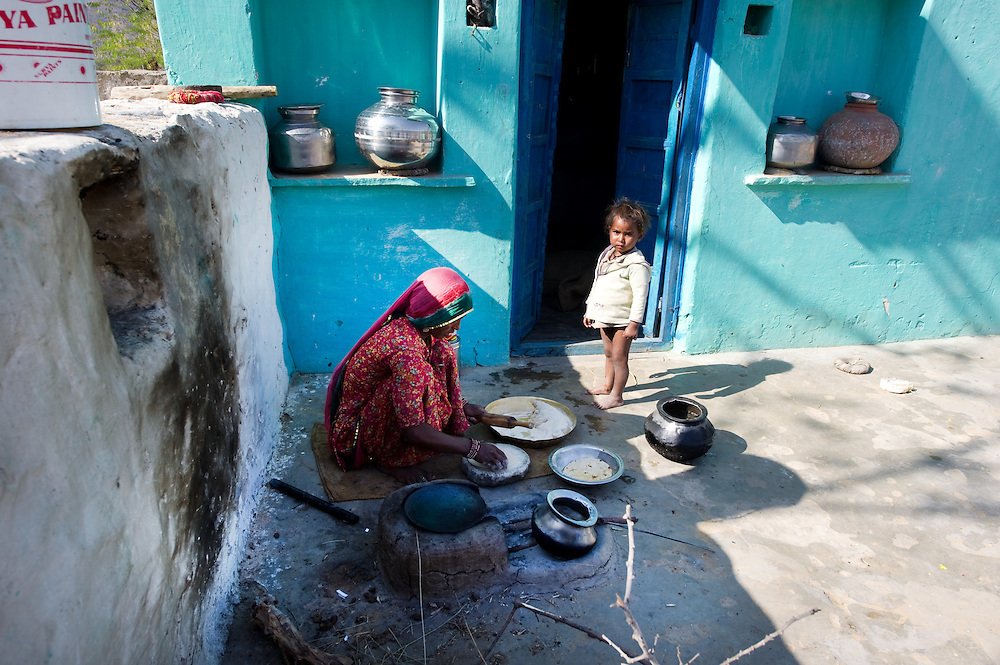 Rajasthani woman prepares food (chapatti) in a courtyard in front of her house. A chulha (oven) with firewood is used to heat.
