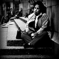 An older woman sitting on steps looking dejected