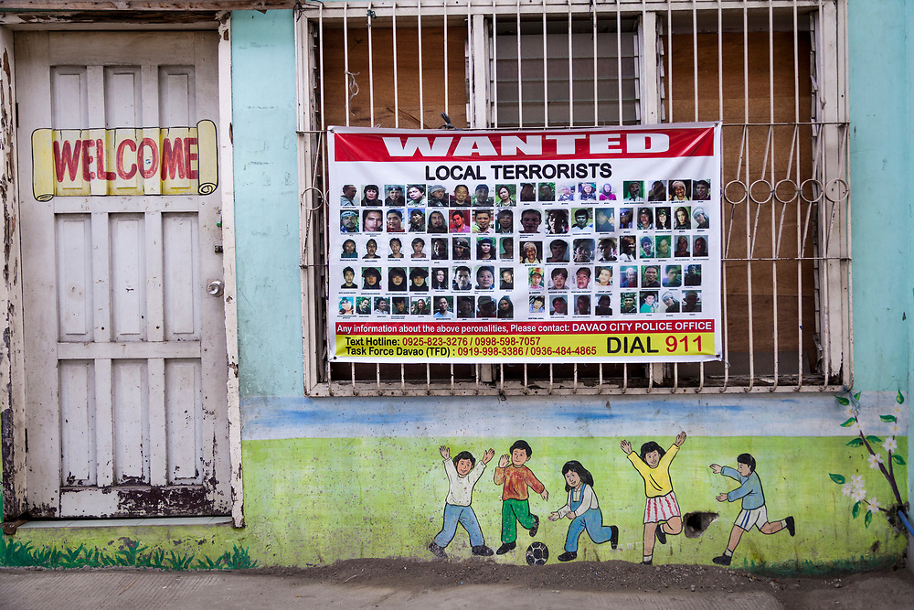 Davao City, Mindanao, Philippines - JUNE 22: Posters of Wanted Terrorists are posted at Mini Forest Barangay 23C.  Thousands have fled Marawi to flee the ongoing conflict after the ISIS backed Maute Group has sieged the city. Currently, over 570 families and roughly 2500 evacuees from Marawi reside in the Mini Forest.