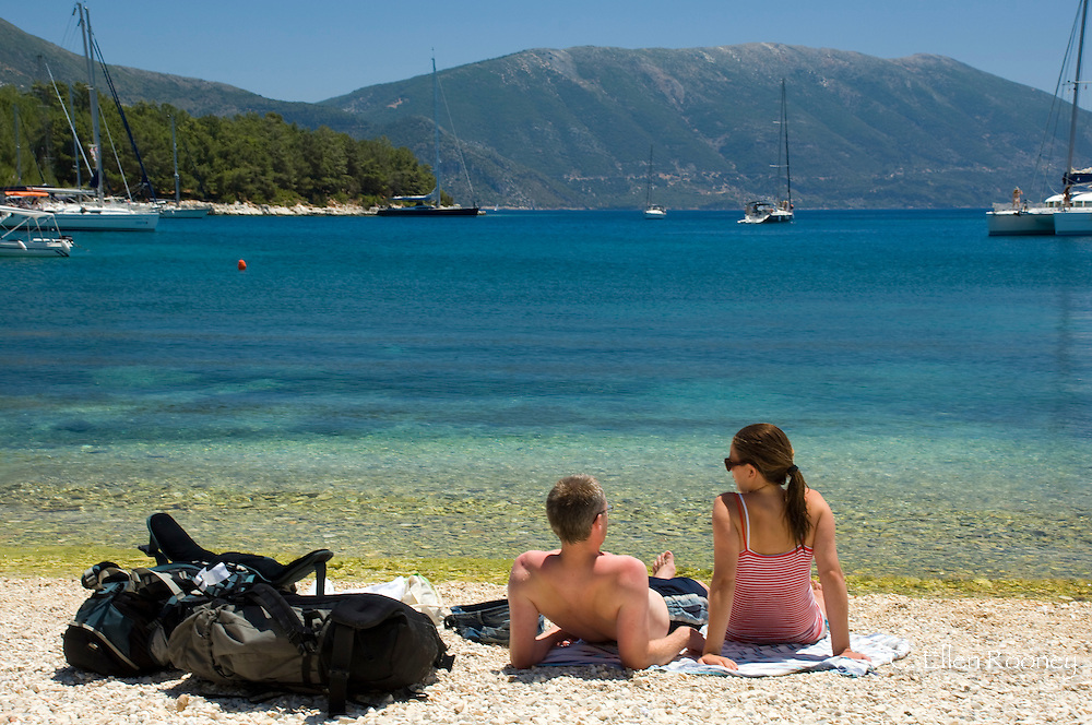 A couple sitting on the beach with their backpacks in Fiskardo, Kefalonia, The Ionian Islands, Greece