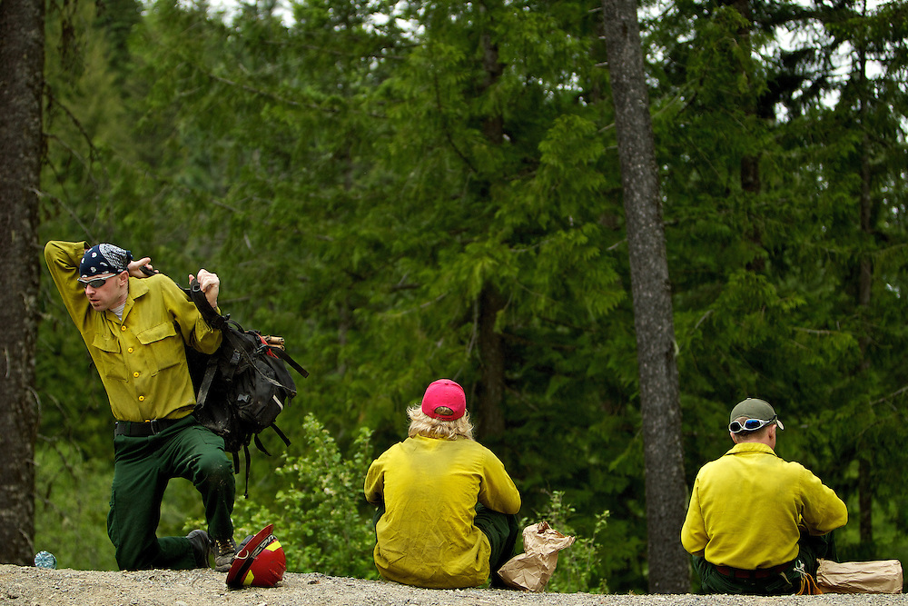 Ashley Kinsey, an Idaho Department of Lands firefighter, puts on his pack after eating lunch Thursday with his crew members.