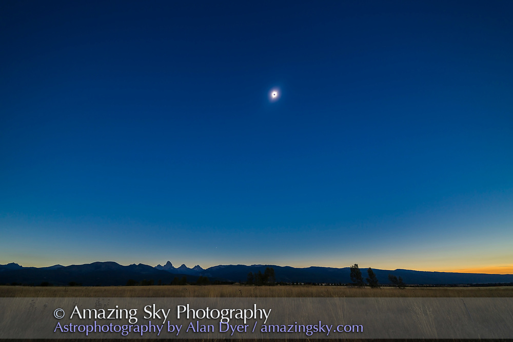 The August 21, 2017 total solar eclipse over the Grand Tetons as seen from the Teton Valley in Idaho, near Driggs. <br /> <br /> This is from a 700-frame time-lapse and is of third contact just as the second diamond ring is starting and the dark shadow of the Moon is receding to the east at left. The sky is darker to the left but the foregound is beginning to light up as the sky to the west off camera to the right brightens and lights the scene. <br /> <br /> Jupiter is just above the Tetons at bottom. <br /> <br /> With the Canon 6D and 14mm SP Rokinon lens at f/2.5 for 1/5 second at ISO 100.