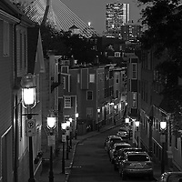 Boston Black and White photography showing a none familiar view of the Boston skyline at twilight including landmarks such as John Hancock building, now known as 200 Clarendon and Leonard P. Zakim Bunker Hill Memorial Bridge. Photograph taken from Pleasant Street in Charlestown, MA near the Bunker Hill Monument, end of the famous Boston Freedom Trail. <br />
