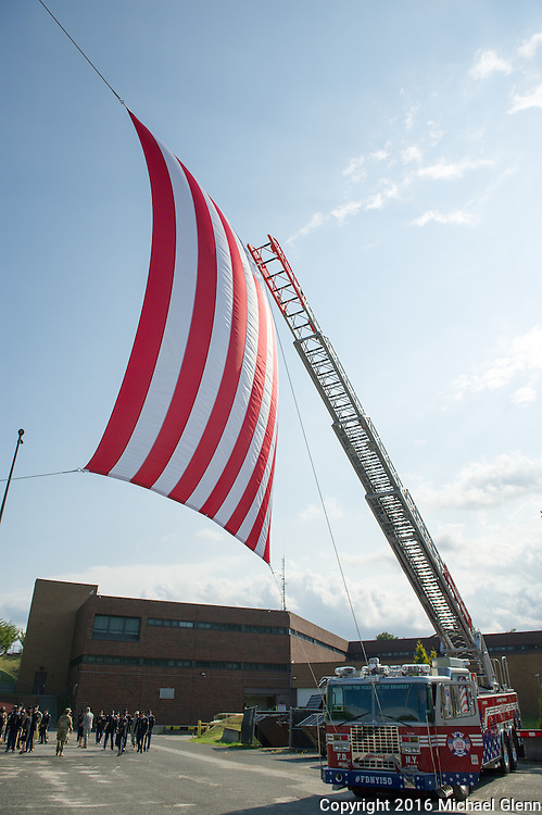 Sept 11, 2016, Bayside, NYC //  US Flag suspended between to FDNY ladder trucks to honor the fallen of the FDNY.  Members of the 77th RRC (USAR) gather at Fort Totten to remember members of the FDNY, that were also members of the USAR killed in the 9/11 attacks  //  Michael Glenn/ Glenn Images