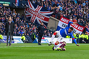 James Tavernier (C) of Rangers FC gets taken out by Ryotaro Meshino of Hearts during the Betfred Scottish League Cup semi-final match between Rangers and Heart of Midlothian at Hampden Park, Glasgow, United Kingdom on 3 November 2019.