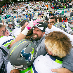 Mountain View coach Judd Benedict (center) celebrates with his players at the conclusion of the 5A championship game against Capital held at Albertsons Stadium in Boise, Idaho. Mountain View defeated Capital 48-21. Saturday November, 19, 2016.