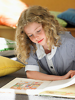 Elementary schoolgirl reading book lying on floor