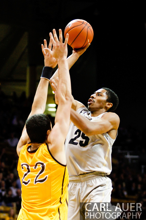 November 13th, 2013:  Colorado Buffaloes junior guard Spencer Dinwiddie (25) attempts a shot over University of Wyoming Cowboys junior forward Larry Nance Jr. (22) in the first half of the NCAA Basketball game between the University of Wyoming Cowboys and the University of Colorado Buffaloes at the Coors Events Center in Boulder, Colorado