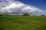 As a storm approaches, a spectacular cumulo-nimbus 'cloud street' forms over Silbury Hill, near Avebury, Wiltshire. The deep blue sky and the yellow of the meadow buttercups in the grass make for a colourful composition. This photograph was taken from West Kennet Long Barrow on the hill opposite.<br />