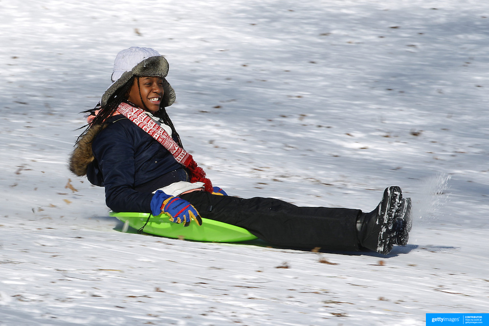 A girl sledding in Central Park after New York City was hit with over 7 inches of snow during its first winter storm of the year. Central Park, Manhattan, New York, USA. 4th January 2014 Photo Tim Clayton