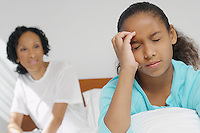 Nurse watching girl (7-9) with migraine in hospital