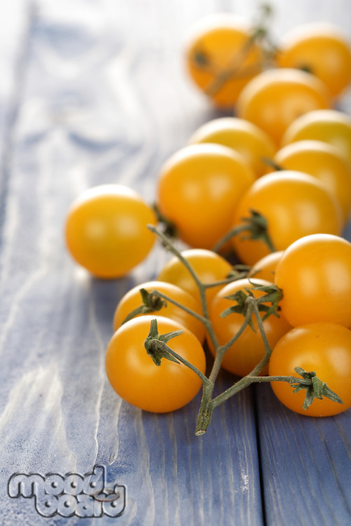 Bunch of yellow cherry tomatoes on wooden table
