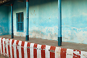 Thinnai (raised platform at the front of a home) with wall painted in red and white. Nagapattinam.