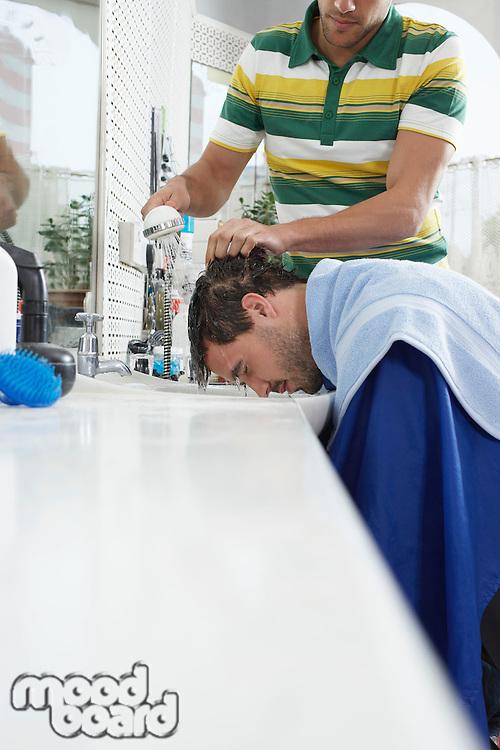 Barber washing mans head in barber shop
