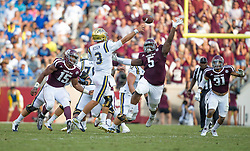 UCLA quarterback Josh Rosen (3) is pressured by Texas A&M's defensive lineman Myles Garrett (15) and Daylon Mack (5) during the fourth quarter of an NCAA college football game Saturday, Sept. 3, 2016, in College Station, Texas. Texas A&M won 31-24. (AP Photo/Sam Craft)