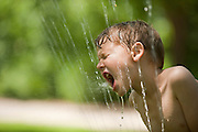 A boy tries to take a drink from a water sprinkler.