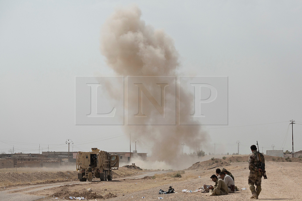 © Licensed to London News Pictures. 30/09/2015. Kirkuk, Iraq. Kurdish peshmerga are seen with an EOD armoured vehicle after the destruction of one of many IEDs around the village of Mansoria near Kirkuk, Iraq.<br /> <br /> Supported by large amounts of coalition airstrikes, members of the Iraqi-Kurdish peshmerga today (30/09/2015) took part in an offensive to take seven villages across a large front near Kirkuk, Iraq. By mid afternoon the Kurds had reached most of their objectives, but suffered around 10 casualties all to improvised explosive devices. All seven villages were originally Kurdish and settled with other ethnic groups during the Iraqi Arabisation process of the 1970's and 80's. Photo credit: Matt Cetti-Roberts/LNP
