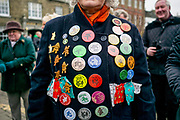 UNITED KINGDOM, Whittlesey: Straw Bear Festival. A local woman shows her continued support and attendance for the Straw Bear festival this weekend with her annual badges. The three day festival, which originated in 1882, consists of traditional Molly, Morris, Clog and Sword dancing as well as parading a large straw character known as 'The Bear' through the town. Rick Findler  / Story Picture Agency