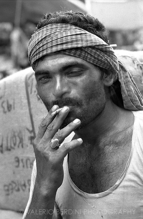 A street porter takes a cigarette break. Most of items in town are brought by porters because of the traffic and the low cost of human work