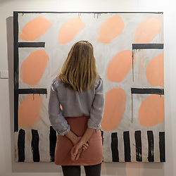 © Licensed to London News Pictures. 05/10/2018. LONDON, UK. Artist Rosa Roberts poses with one of her works as part of Not 30%, a sub-exhibition presenting works by female artists. Opening day of The Other Art Fair, presented by Saatchi Art, which runs until 7 October in Bloomsbury.  The fair, which coincides with Frieze Week, is a collection of artworks by independent and emerging artists handpicked by a committee of art world experts.  Visitors and art buyers have the opportunity to meet the artists presenting their work at the fair. Photo credit: Stephen Chung/LNP