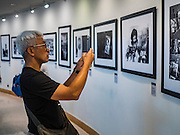 "06 NOVEMBER 2016 - BANGKOK, THAILAND: A Thai uses a smart phone to make a picture of one of the pictures in the photo exhibit honoring Bhumibol Adulyadej, the late King of Thailand. The Royal Photographic Society of Thailand with the Bangkok Art and Culture Centre and Thai Beverage Public Company Limited are hosting a photography exhibition to commemorate the late Thai King Bhumibol Adulyadej. The ""In Remembrance of His Majesty King Bhumibol Adulyadej"" Photography Exhibition is dsiplaying 89 photographs by 89 photographers honoring King Bhumibol Adulyadej's legacy. The King was an avid photographer was usually seen with a camera in his hands. The exhibition will be on display until 27 November 2016 on the Curved Walls on the 3rd - 5th floor, Bangkok Art and Culture Centre.     PHOTO BY JACK KURTZ"
